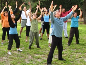 group practicing qigong with arms raised