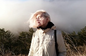 woman in sun hair blowing clouds